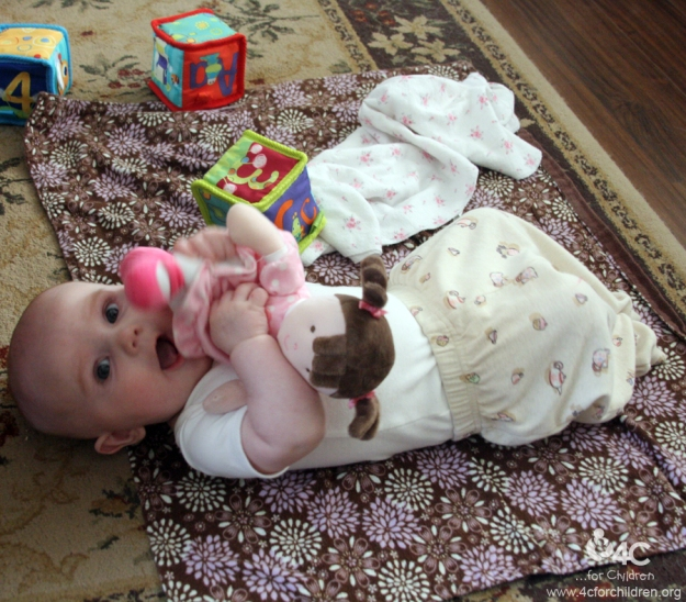 Lay a blanket on the carpet and place toys within an infant's reach to encourage movement.